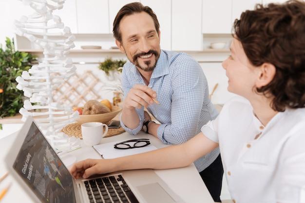 Красивый умный мальчик обсуждает глобальные торговые переводы со своим отцом, в то время как отец смеется и с гордостью смотрит на сына