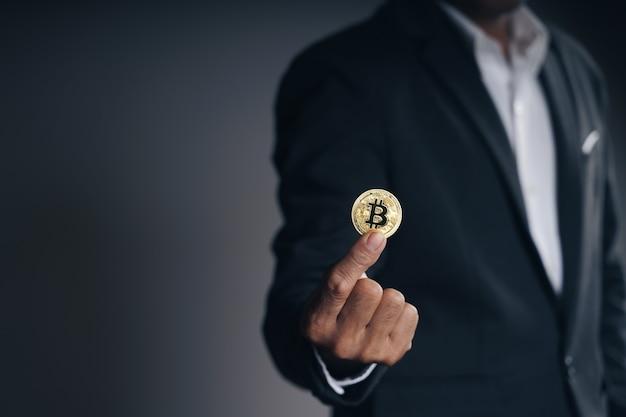 Красивый инвестор бизнесмен в черном костюме, держащий золотой биткойн на темном фоне, торговля, криптовалюта, цифровая виртуальная валюта, альтернативные финансы и инвестиционная концепция.