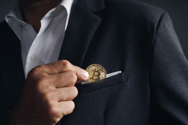Красивый бизнесмен-инвестор положил золотой биткойн в карман костюма на темном фоне, торговля, криптовалюта, цифровая виртуальная валюта, альтернативные финансы и инвестиционная концепция.