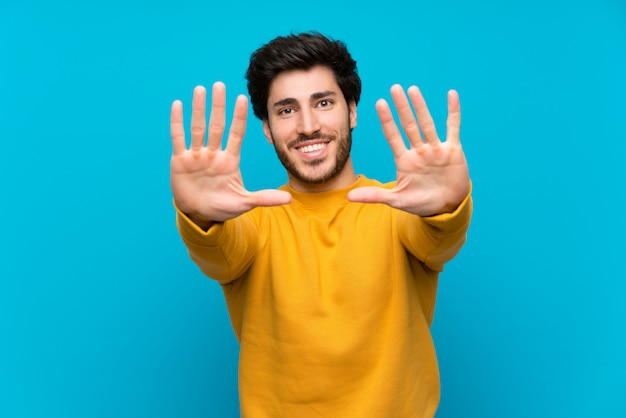Handsome over isolated blue wall counting ten with fingers