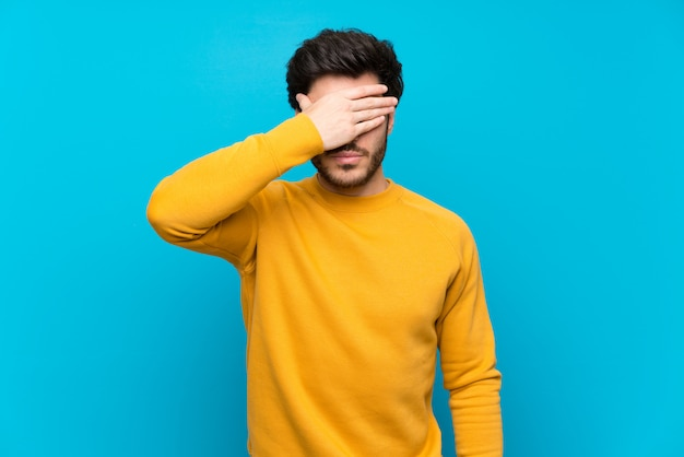 Handsome over isolated blue wall covering eyes by hands. do not want to see something