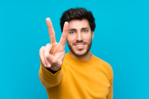 Handsome over isolated blue wall smiling and showing victory sign