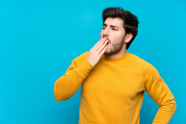 Handsome over isolated blue wall yawning and covering wide open mouth with hand