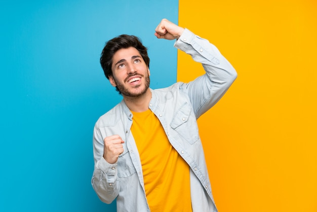 Handsome over isolated colorful background celebrating a victory