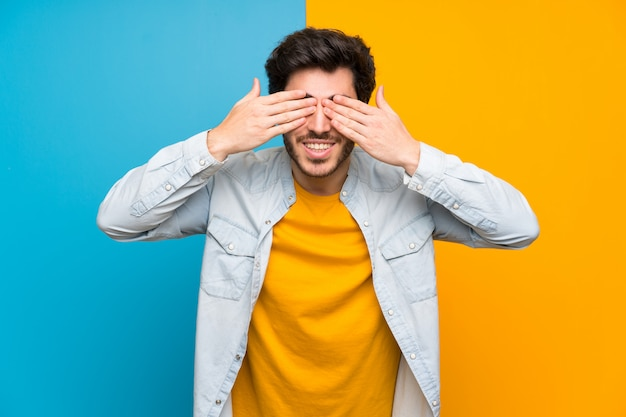 Handsome over isolated colorful background covering eyes by hands