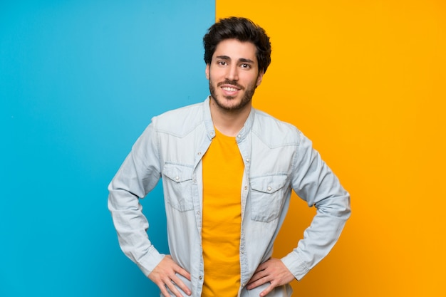 Handsome over isolated colorful background posing with arms at hip and smiling