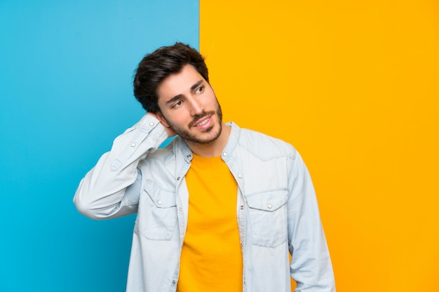 Handsome over isolated colorful background thinking an idea