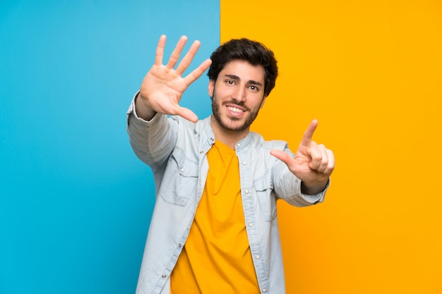Handsome over isolated colorful  counting seven with fingers