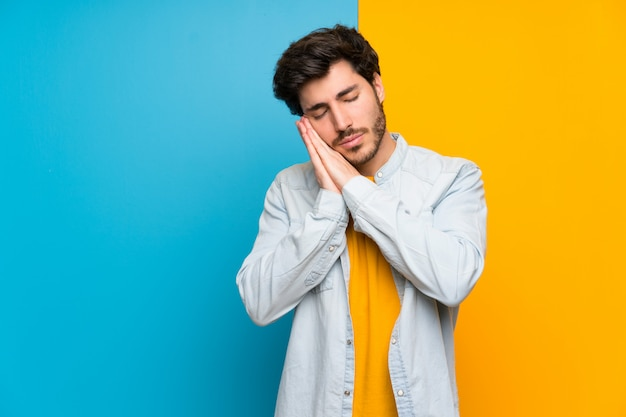 Handsome over isolated colorful making sleep gesture in dorable expression