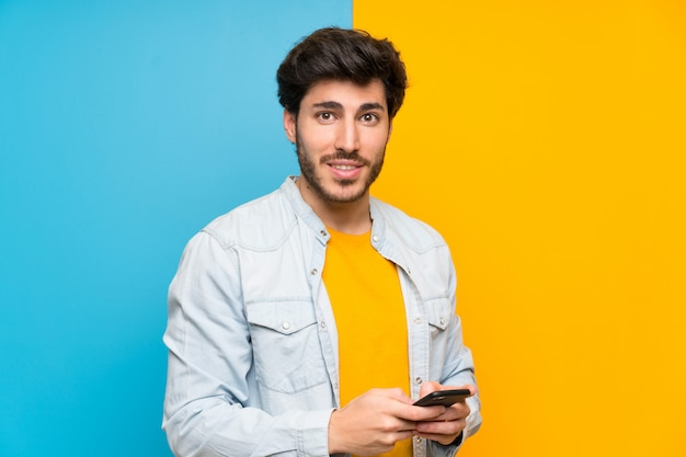 Handsome over isolated colorful wall sending a message with the mobile