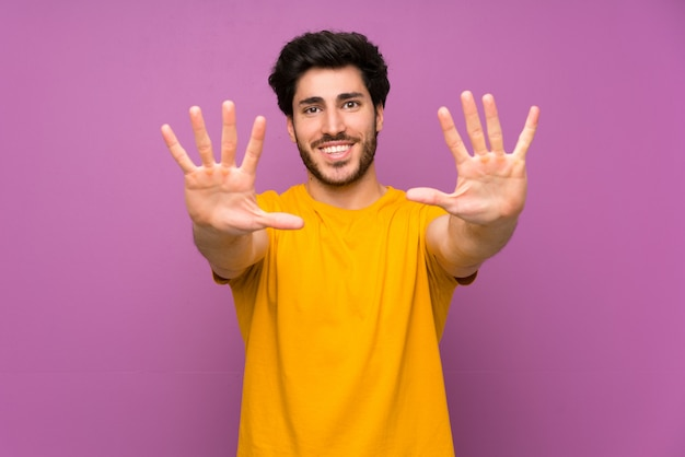 Handsome over isolated purple wall counting ten with fingers