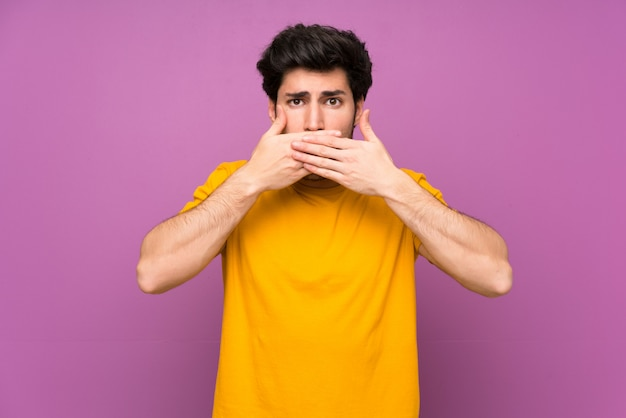 Handsome over isolated purple wall covering mouth with hands