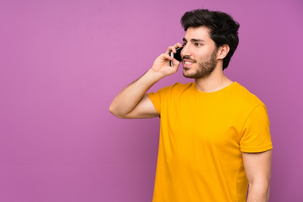 Handsome over isolated purple wall keeping a conversation with the mobile phone