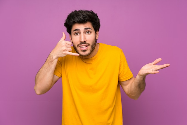 Handsome over isolated purple wall making phone gesture and doubting