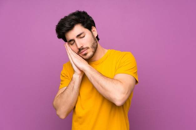 Handsome over isolated purple wall making sleep gesture in dorable expression