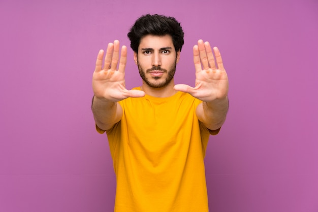 Handsome over isolated purple wall making stop gesture and disappointed