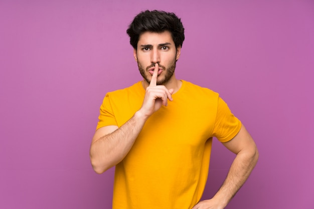 Handsome over isolated purple wall showing a sign of silence gesture putting finger in mouth
