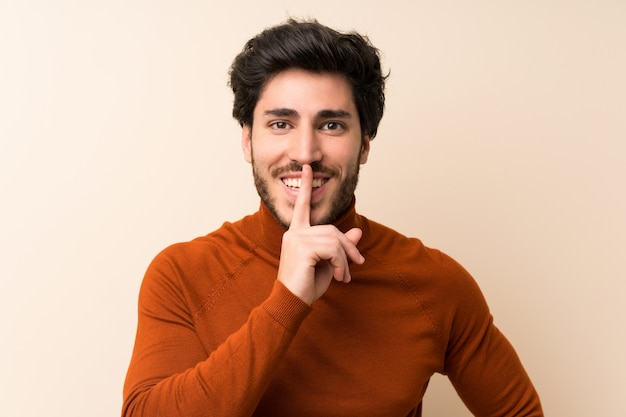 Handsome over isolated wall doing silence gesture