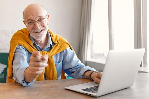 Красивый радостный возбужденный пожилой мужчина с серой щетиной, работающий на ноутбуке в современном офисном интерьере, сидя за столом у окна, улыбаясь и указывая указательным пальцем на камеру. выборочный фокус