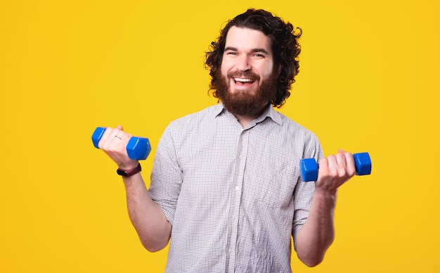 Handsome and joyful man in casual working with small dumbbells