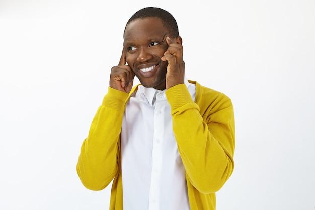 Красивый радостный молодой темнокожий мужчина в стильной одежде, счастливо улыбаясь, массирует виски пальцами, чтобы заставить его мозг работать, обдумывая решение проблемы. люди и язык тела
