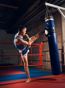 Handsome kick boxer training kicking and punching boxing bag