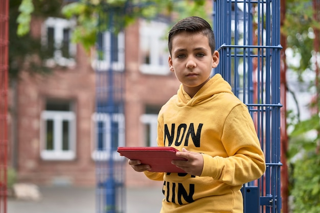 Handsome kid using his digital tablet on the street