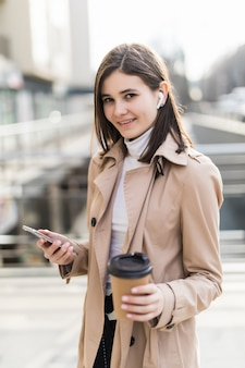 Handsome lady drinks coffee and read news on her phone outside