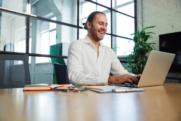 Красивый смеющийся мужчина с щетиной работает с ноутбуком, сидя за столом в современном офисе