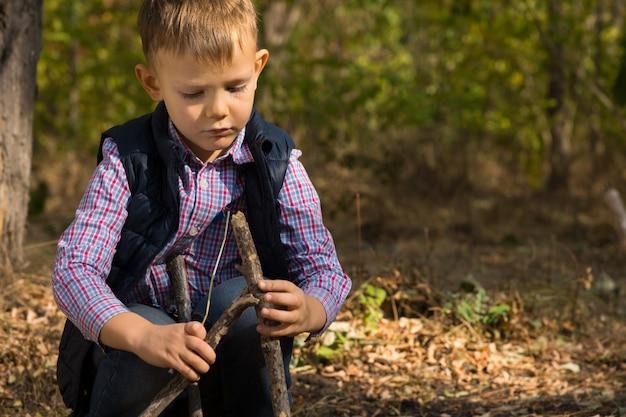 Красивый маленький мальчик, строящий небольшой вигвам из деревянных прутьев и веток, играет на открытом воздухе в лесу
