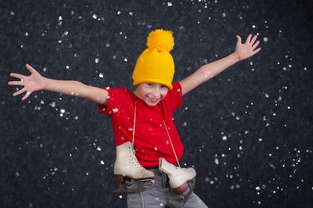 Красивый маленький мальчик в вязаной желтой шляпе с винтажными коньками на сером фоне.