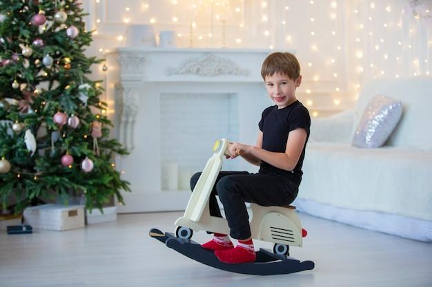 Красивый маленький мальчик в повседневной одежде играет в рождественской комнате.