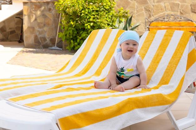 Красивый маленький мальчик в солнечных очках и бандане сидит на шезлонге у бассейна. выборочный фокус.