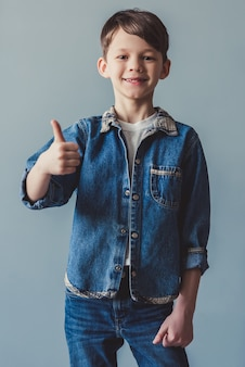 Handsome little boy in jean clothes is showing ok sign.