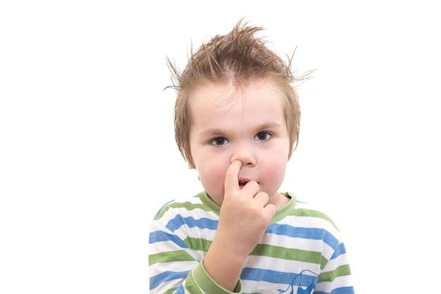 흰색 배경에 고립 된 그의 코를 따기 잘 생긴 어린 소년