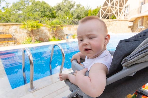 잘생긴 소년은 수영장 옆 유모차에 앉아 있습니다. 선택적 초점