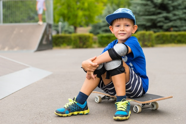 Handsome little boy sitting on his skateboard in his safety gear smiling at the camera as he takes a break at the skate park