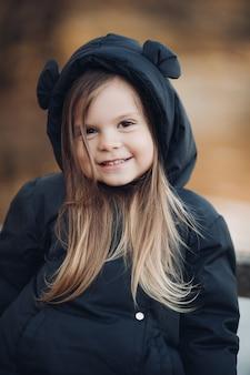 Una bella bambina con lunghi capelli castani e un bel sorriso in giacca nera va a fare una passeggiata nel parco in autunno