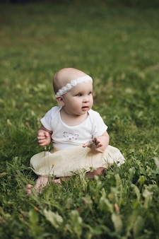 Handsome little girl with short fair hair and pretty smile in white dress sits on a grass in the park in summer and smiles