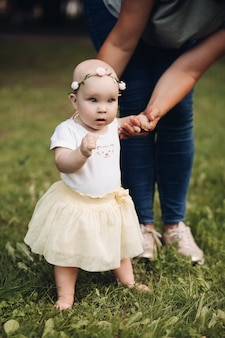 Handsome little girl with short fair hair and pretty smile in white dress sits on a grass in the park in summer with her mother