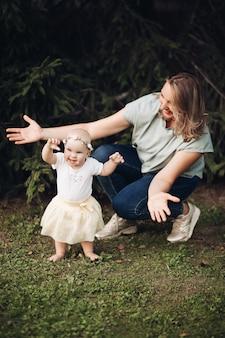Una bella bambina con i capelli corti e biondi e un bel sorriso in abito bianco si siede su un prato nel parco in estate con sua madre