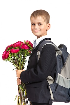 Handsome little schoolboy is holding flowers isolated. back to school