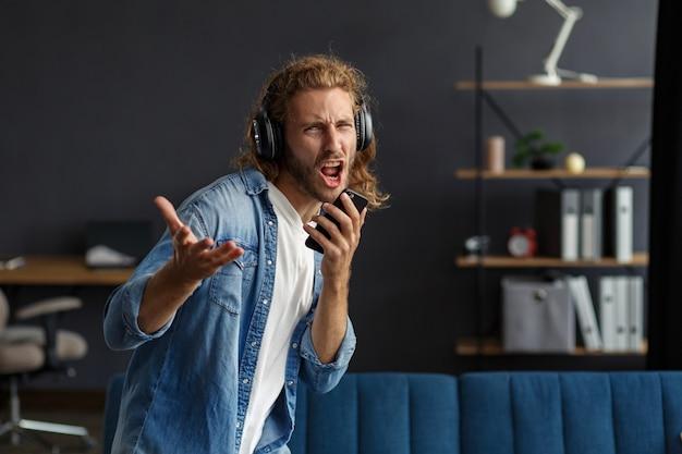 헤드폰을 끼고 음악을 듣고 노래하고 춤을 추고 있는 잘생긴 장발 곱슬머리 남자. 이어폰과 휴대전화를 든 웃긴 감정적인 웃는 남자는 집에서 휴식을 취합니다. 음악을 들으며 즐기세요. 스트레스 관리.