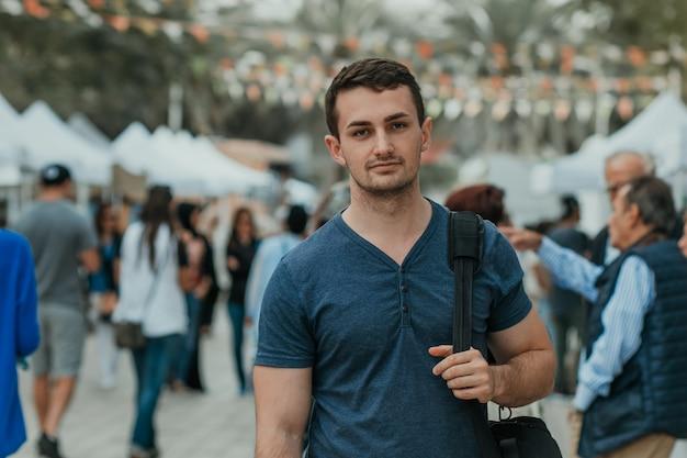 バックパックでカメラを見ているハンサムな男留学生男性