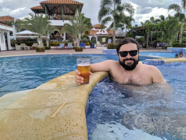Handsome looking man with beard in a pool holding a glass of beer
