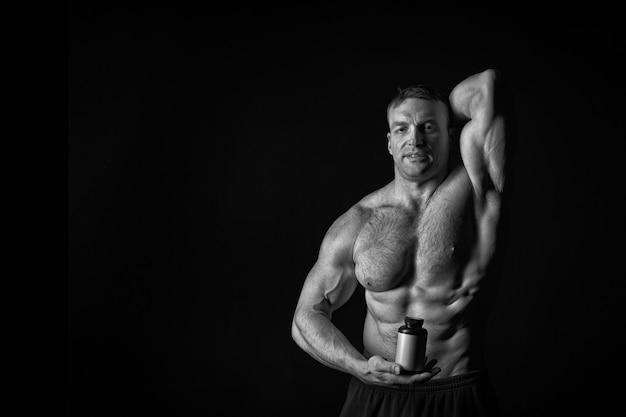 Красивый мачо или сексуальный мускулистый парень с телом спортсмена и торсом держит пластиковую банку или контейнер с питанием или таблетками на черном фоне