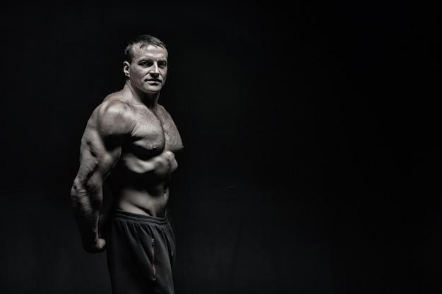 Красивый мачо или сексуальный мускулистый парень с телом спортсмена и тренировкой торса и позированием на черном фоне, копией пространства