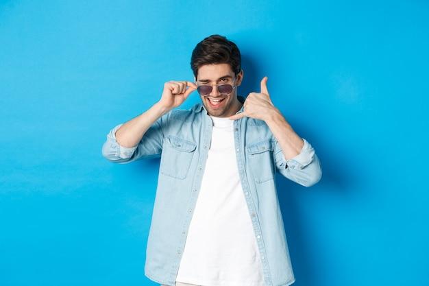 Bell'uomo macho in occhiali da sole che flirta con te, fa il segno del telefono e fa l'occhiolino, chiamami gesto, in piedi su sfondo blu.