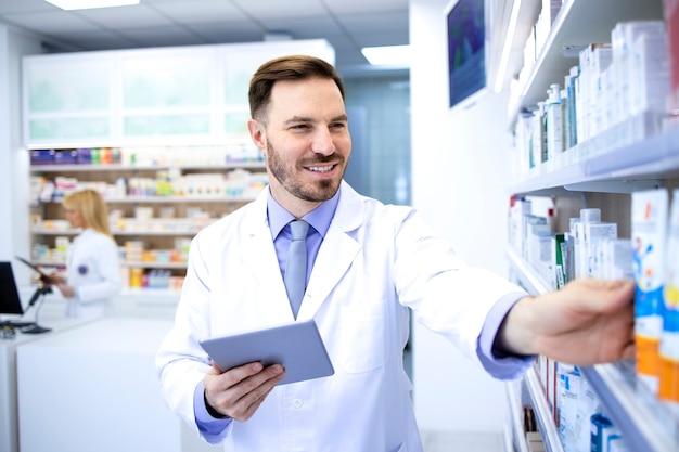 Красивый мужской аптекарь в белом халате, работающий в аптеке или аптеке.