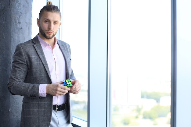 Handsome male architect wearing casual clothes holding rubik's cube.